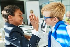 Two kids confirm deal with a high five. Two multicultural kids confirm deal with a high five in business start-up royalty free stock photo