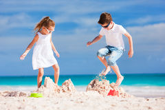 Two kids crushing sandcastle Royalty Free Stock Photo