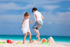 Two kids crushing sandcastle Stock Photography