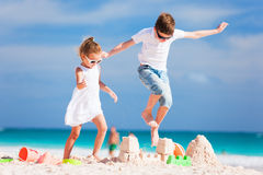 Two kids crushing sandcastle Stock Photo