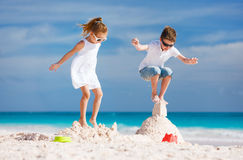 Two kids crushing sandcastle Royalty Free Stock Image