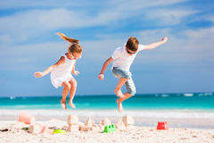 Two kids crushing sandcastle Royalty Free Stock Images