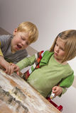 Two kids cutting cookies for christmas Stock Photo