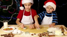 Two kids cutting the dough stock video