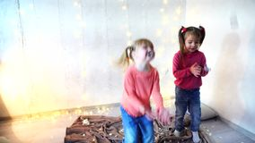 Two kids dancing at home christmas party. Two children dancing at home christmas party on lights background on New Year eve. Girld having fun and foolign aroung stock footage