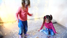 Two kids dancing at home christmas party. Two children dancing at home christmas party on lights background on New Year eve. Girld having fun and foolign aroung stock video
