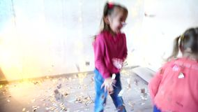 Two kids dancing at home christmas party. Two children dancing at home christmas party on lights background on New Year eve. Girld having fun and foolign aroung stock video footage