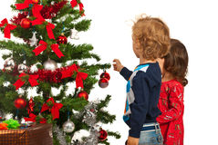 Two kids decorate Christmas tree Stock Image
