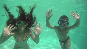 Two kids diving in swimming pool. Underwater slow motion stock video footage