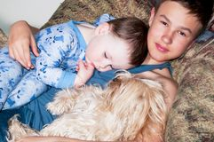 Two kids and a dog resting in a chair royalty free stock image