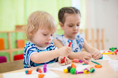 Two kids doing arts and crafts in day care centre Stock Photos