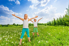 Two kids doing outdoor gymnastics on the grass Royalty Free Stock Photos
