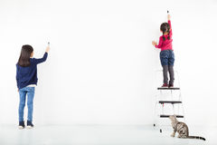 Two kids drawing on the blank white wall stock images