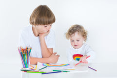 Two kids drawing with colorful pencils Stock Photo