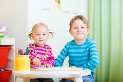 Two kids drawing with coloring pencils. Portrait of two small kids drawing with coloring pencils Stock Photo