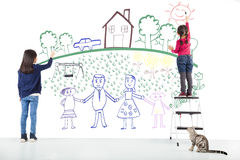 Two kids drawing their dream on the white wall. At home Stock Image