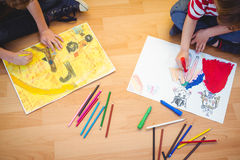 Two kids drawing together on sheets Royalty Free Stock Photos