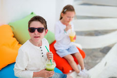 Two kids drinking smoothies outdoors Royalty Free Stock Images
