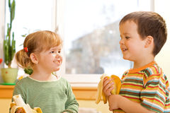 Two kids eating bananas Stock Photography
