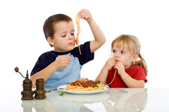 Two kids eating pasta with their hands stock images