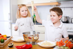 Two kids eating spaghetti Stock Images