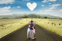 Two kids embrace their father on the road Royalty Free Stock Photos
