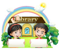 Two kids with empty signboards standing in front of the library Stock Photo