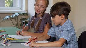 Two kids enjoying talking and drawing at art class together. Little boy chatting to his classmate while drawing. Cute red haired girl coloring with her friend royalty free stock photo