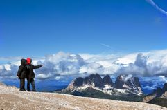 Two kids exploring mountains. Two brothers exploring mountains and pointing on great panorama Stock Images