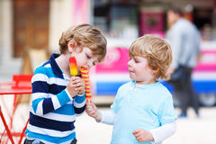Two kids feeding each other with ice cream Stock Image