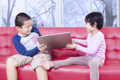 Two kids fighting to take over laptop Royalty Free Stock Image