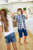 Two kids fighting with wooden spoons in fun Stock Image