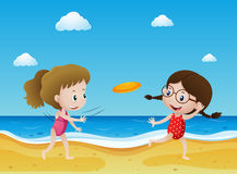 Two kids flying frisbee on the beach Stock Photos