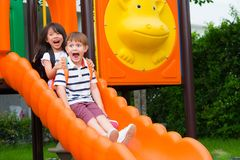 Two kids friends having fun to play together on children`s slide at school playground,back to school activity.  royalty free stock image