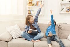 Two kids with gadgets on couch at home. Two kids with gadgets. Siblings with raised hands won online game on tablet. Happy children celebrating success. Family Royalty Free Stock Photo
