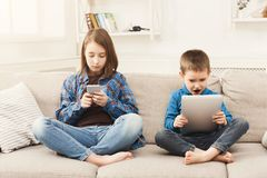 Two kids with gadgets on couch at home. Two kids with gadgets. Sister and brother surfing the net or playing online games on smartphone and digital tablet at Stock Photos