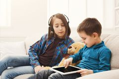 Two kids with gadgets on couch at home. Two kids with gadgets. Sister listening to music, brother sharing funny content on digital tablet on sofa at home. Family Stock Photo