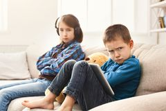 Two kids with gadgets on couch at home. Two kids with gadgets. Sister listening to music, offended brother using digital tablet on sofa at home. Family Stock Photography