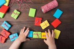 Two kids hand to lay out ready gift boxes in one line Stock Images