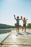 Two kids having fun and jumping at the lake Stock Photography