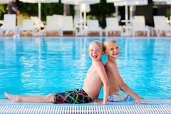 Two kids having fun in summer swimming pool Royalty Free Stock Photos