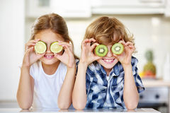 Two kids hiding eyes behind fruits. Two kids in kitchen hiding their eyes behind fruits Royalty Free Stock Images