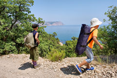 Two kids hiking on rocks next to sea Royalty Free Stock Photo
