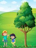 Two kids at the hilltop near the tree Royalty Free Stock Images