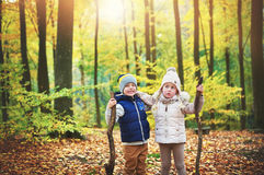 Two kids holding branches in autumn forest Stock Images