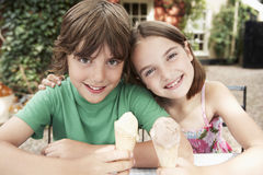 Two Kids With Ice Cream Cones At Outdoor Table Royalty Free Stock Photography