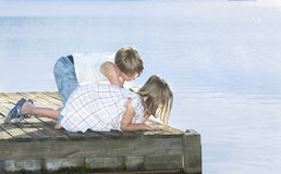 Two kids on a jetty. Looking down into the water and watching fishes Stock Photography