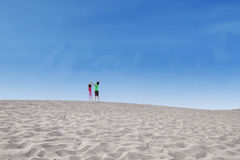 Two kids jump on desert Stock Photography