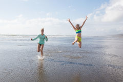 Two kids jumping at the beach Royalty Free Stock Images
