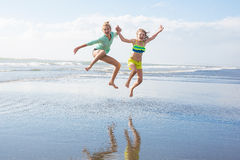 Two kids jumping at the beach Stock Image